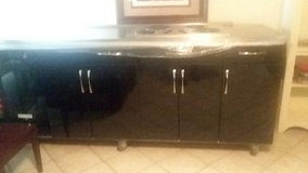 Counter stove top with small fridge trash bin and mirror in Plainfield, Illinois