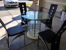 Modern glass dinning table with 4 chairs in Fort Carson, Colorado