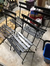 4 black folding chairs in Conroe, Texas