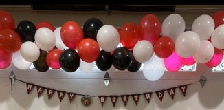 Red, black, white balloon arch in Yucca Valley, California